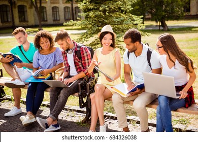 Cheerful students teenagers in casual outfits with note books and devices are studying outdoors. Classmate, international friendship, summer, communication, education and teenage concept