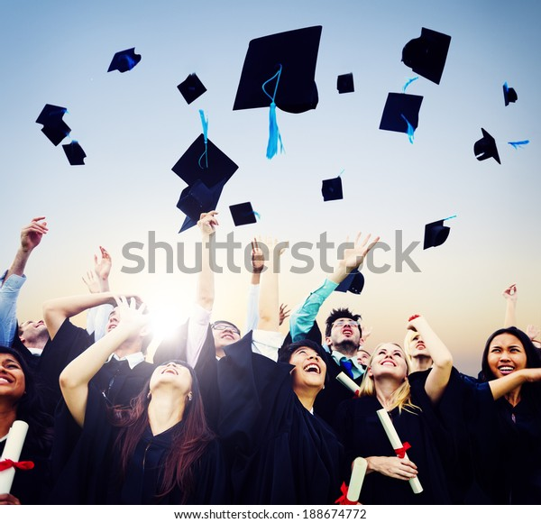 Cheerful students throwing graduation caps in the Air