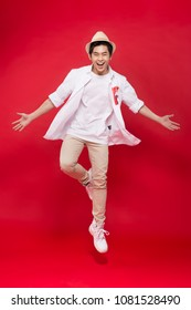 Cheerful stylish asian young male man jumping isolated on red background