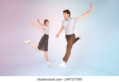 Cheerful stylish couple is dancing vintage joyful jazz dance called lindy hop indoors in the studio on colored background