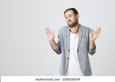 Cheerful stylish fashionable bearded guy in trendy jacket over white t-shirt raises hands as shows being uninvolved, has happy look. Caucasian male gestures in studio. I am not guilty!