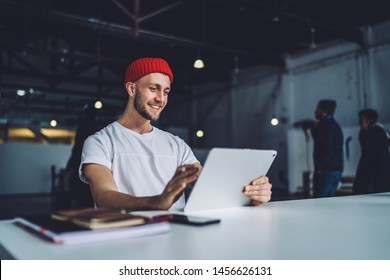 Cheerful stylish hipster man in white t-shirt sitting at table in modern garage coworking space and browsing modern tablet gadget