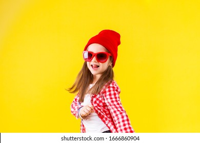 Cheerful stylish little girl dressed in pink checkered shirt, red cap, sunglasses, jeans is jumping on yellow background. Smiling cute child is dancing, having fun. Emotional portrait concept.