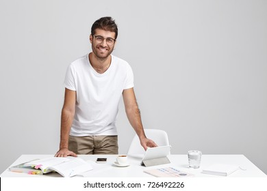 Cheerful stylish male freelancer being glad to have successful day, rejoices finishing work, stands at white table with necessary documents and modern gadget. Scientific researcher develops new theory