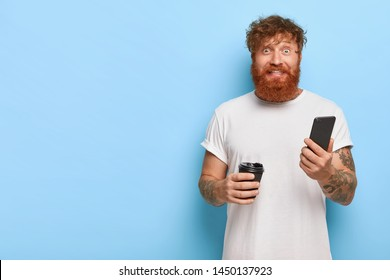 Cheerful stylish man with red hairstyle, thick beard, happy get message from lover, uses modern gadget, drinks coffee, stands against blue wall with empty space for your text. Technology concept