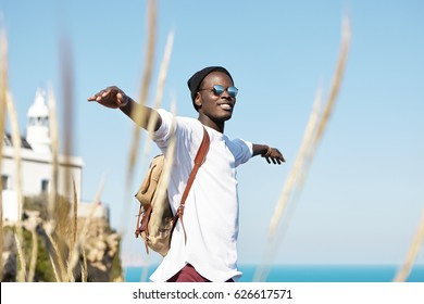Cheerful stylish young African American traveler with backpack smiling joyfully, spreading his arms, feeling free, happy and relaxed, enjoying nice summer day while spending weekend abroad at seaside