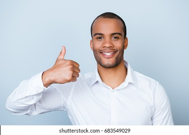 Cheerful successful african employer is showing thumbsup gesture on a pure background, standing in a formal wear, smiling