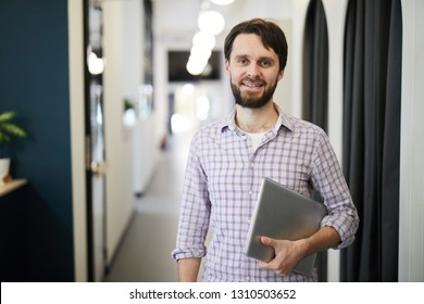 Cheerful successful bearded entrepreneur in checkered shirt standing in corridor and holding laptop while looking at camera