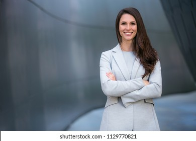 Cheerful successful business woman portrait at executive financial bank building, smiling with arms folded