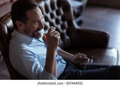 Cheerful successful businessman enjoying his drink