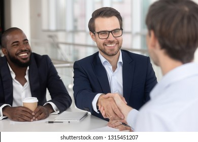 Cheerful successful businessmen meet at boardroom multiracial entrepreneurs starting collaboration negotiations with handshake, make good deal, signing contract, employment and human resources concept