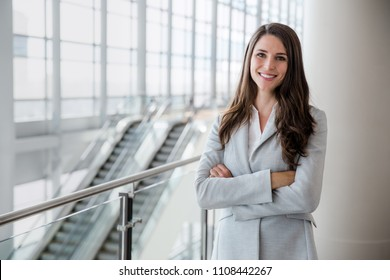 Cheerful successful businesswoman portrait in large financial bank building with arms folded
