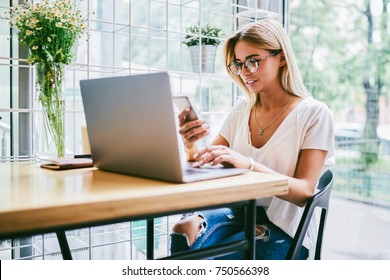Cheerful successful female in eyeglasses received good news on smartphone while working at computer.Positive copywriter in spectacles sitting at table with laptop device and reading post on website