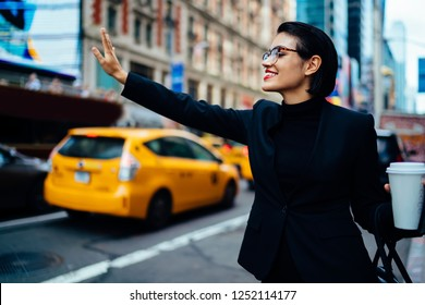 Cheerful successful woman hailing rideshare taxi car on road for getting to business meeting with partners, happy smiling female with hand up calling cab on modern street in financial district