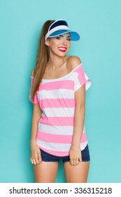 Cheerful Summer Girl. Beautiful young woman in striped pink shirt and blue plastic cap. Three quarter length studio shot on teal background.