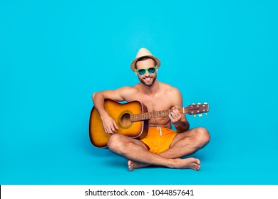 cheerful, talented guy with stubble in yellow shorts  sitting with crossed legs over blue background, having guitar in hands, playing songs, looking at camera, entertains the company of friends