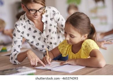Cheerful teacher helping her student
