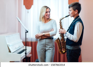 Cheerful teacher with student boy learning saxophone lessons at music school