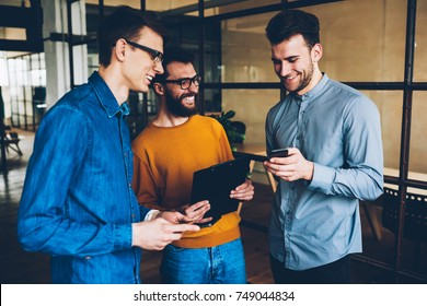 Cheerful team members having fun on break watching video on smartphone and joking, happy group of skilled programmers satisfied with success if job celebrating completing of project together