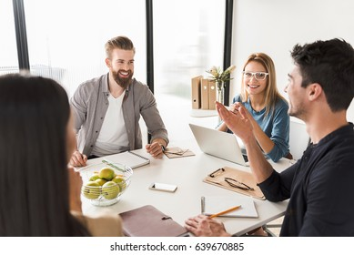Cheerful team is sitting around table in office. They are discussing certain case with smile and enthusiasm
