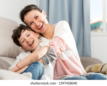 Cheerful teen boy with his mother embracing while sitting on sofa at home