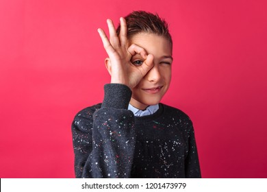Cheerful teen boy showing OK sign isolated on red background