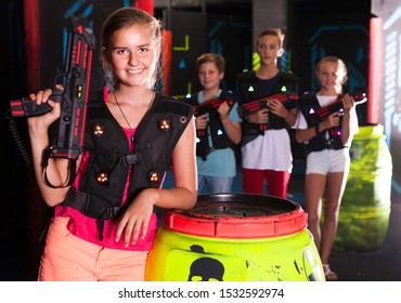 Cheerful teen girl standing with laser pistol in dark lasertag room during game with friends