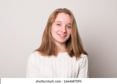 Cheerful teen girl. Studio image of a cute smiling young girl on a gray background.