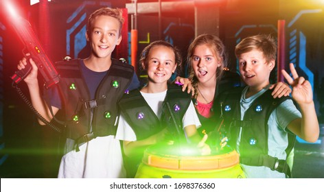 Cheerful teen girls and boys with laser pistols posing together in dark laser tag labyrinth