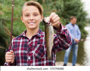 Cheerful teenage boy holding catch freshwater fish in hands on weekend