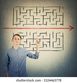 Cheerful teenage boy pointing index finger up showing the solution to escape from labyrinth. Young student breaking the rules, as red line pierce the maze walls. Different thinking genius concept.