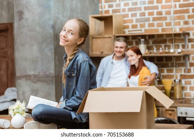 cheerful teenage girl with book looking at camera while parents unpacking boxes at new home