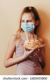 fröhliches Teenagermädchen im Gesicht mit Maske und mit einem auf die Seite schauenden Pferdeschwanz hält einen Kuchen in den Händen und feiert ihren Geburtstag allein und sorgt sich um die Folgen des Coronavirus