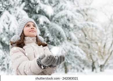 Cheerful, teenage girl looking in the sky, catching a snowflakes.Copy space