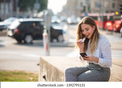 Cheerful teenage girl reacting to a funny message on her phone