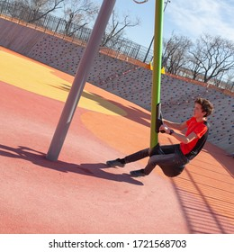 Cheerful teenager swinging on a swing in the park at the playground. Child on a summer walk, outdoor