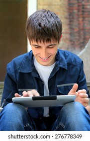 Cheerful Teenager with Tablet Computer on the Street
