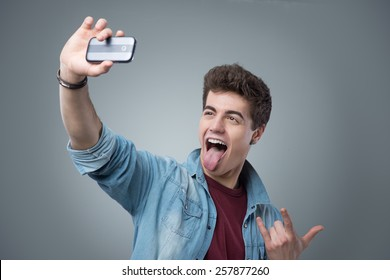 Cheerful teenager taking funny selfies with his mobile phone