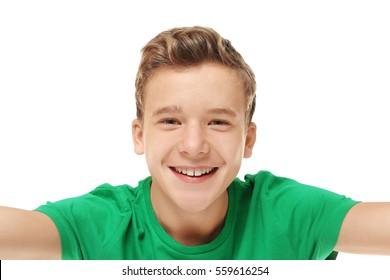 Cheerful teenager taking selfie on white background, closeup