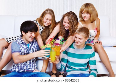 Cheerful teenagers clinking their glasses with party beverages