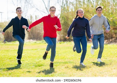 Cheerful teenagers are jogging together in the park and having fun