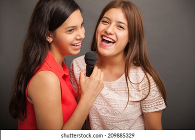 Cheerful teenagers singing a song with a microphone and having fun