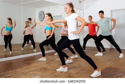 Cheerful teens practicing dance, stretching with young female trainer in dance hall