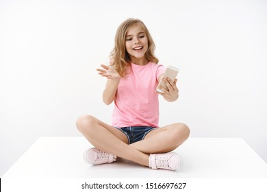 Cheerful tender blond lively enthusiastic young teenage girl, sit crossed legs, hold smartphone, record video-blog become blogger, gesturing excited explain story talking friend, white background