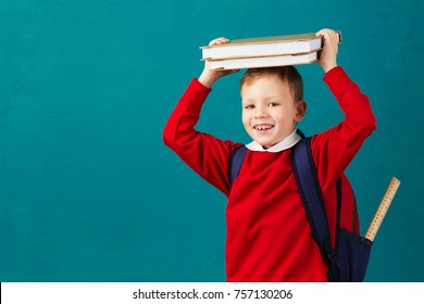 Cheerful thoughtful little school boy in school uniform with backpack and big pile of books standing against blue wall. Looking at camera. School concept. Back to School