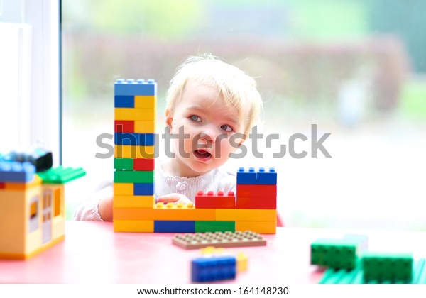 Cheerful toddler girl building house from plastic blocks sitting next to a big window