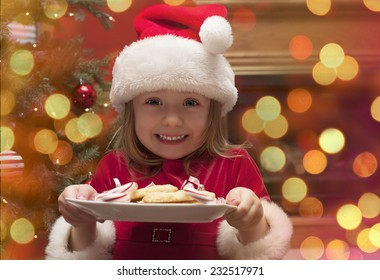 Cheerful toddler girl in hat holding plate with cookies and candy for santa claus