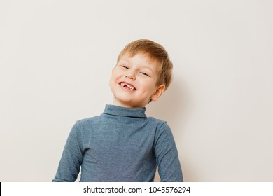cheerful toothless blond boy six years old in striped turtleneck on white background