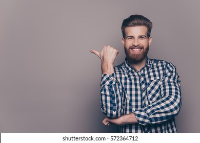 Cheerful toothy bearded stylish man pointing with finger.