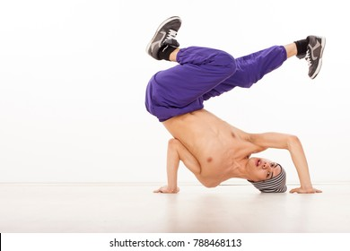 Cheerful topless male dancer sitting on one hand, performing streetdance position , wearing ultraviolet pants, with legs apart and head on the floor. Horizontal image , in studio, on white background